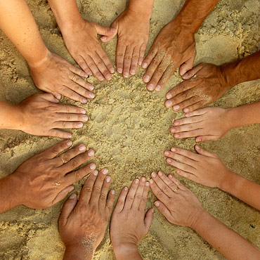 hands in the sand in a circle signifying togetherness and teamwork