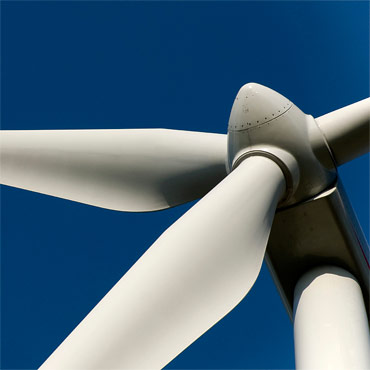square image of renwable energy wind turbine against blue sky